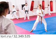 Купить «Tween girl mastering new taekwondo moves during group class with male coach», фото № 32349535, снято 11 июля 2020 г. (c) Яков Филимонов / Фотобанк Лори