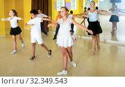 Купить «Children learn dance movements in dance class», фото № 32349543, снято 13 июля 2017 г. (c) Яков Филимонов / Фотобанк Лори