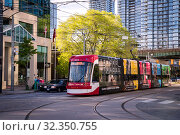 Toronto, Canada - 06 09 2019: A new Bombardier-made TTC streetcar with ad banners on its sides moving along the Spadina avenue in Toronto. Toronto Transit Commission is a public transport agency that operates bus, streetcar and subway. Редакционное фото, фотограф Вадим Роднев / Фотобанк Лори