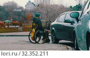 Купить «Disabled man in wheelchair going down the ramp from the footpath and going back on», видеоролик № 32352211, снято 30 мая 2020 г. (c) Константин Шишкин / Фотобанк Лори