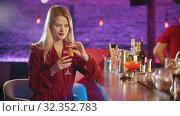 Купить «Gorgeous young woman sitting by the bartender stand - taking the drink from the stand and takes away the straw», видеоролик № 32352783, снято 19 февраля 2020 г. (c) Константин Шишкин / Фотобанк Лори