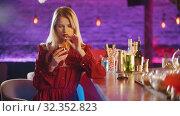 Купить «Gorgeous young woman sitting by the bartender stand - drinking a beverage from the straw», видеоролик № 32352823, снято 19 февраля 2020 г. (c) Константин Шишкин / Фотобанк Лори