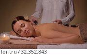 Купить «beautiful woman having hot stone massage at spa», видеоролик № 32352843, снято 19 октября 2019 г. (c) Syda Productions / Фотобанк Лори