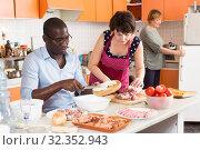 Купить «Happy interracial couple cooking», фото № 32352943, снято 17 августа 2019 г. (c) Яков Филимонов / Фотобанк Лори
