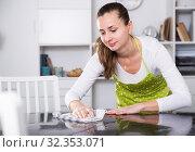 Купить «Young woman in an apron cleans the table at home», фото № 32353071, снято 11 июля 2020 г. (c) Яков Филимонов / Фотобанк Лори