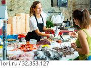Polite worker offering fresh sea bass to woman. Стоковое фото, фотограф Яков Филимонов / Фотобанк Лори