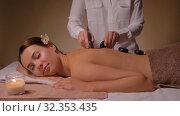 Купить «beautiful woman having hot stone massage at spa», видеоролик № 32353435, снято 19 октября 2019 г. (c) Syda Productions / Фотобанк Лори