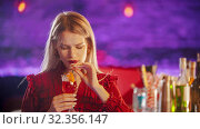 Gorgeous blonde young woman sitting by the bartender stand - drinking a beverage from the straw. Стоковое фото, фотограф Константин Шишкин / Фотобанк Лори