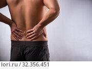 Man suffering from backbain on gray. Стоковое фото, фотограф Elnur / Фотобанк Лори