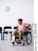 Купить «Young injured man waiting for his turn in hospital hall», фото № 32356615, снято 3 мая 2019 г. (c) Elnur / Фотобанк Лори