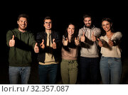 Купить «happy smiling friends showing thumbs up at night», фото № 32357087, снято 31 августа 2019 г. (c) Syda Productions / Фотобанк Лори