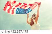 Купить «happy young woman with american flag outdoors», фото № 32357175, снято 31 июля 2016 г. (c) Syda Productions / Фотобанк Лори