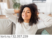 Купить «happy african american young woman at home», фото № 32357239, снято 22 сентября 2019 г. (c) Syda Productions / Фотобанк Лори