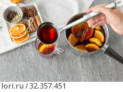 Купить «hand with ladle pouring hot mulled wine to glass», фото № 32357451, снято 4 октября 2018 г. (c) Syda Productions / Фотобанк Лори