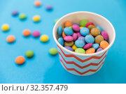 Купить «candy drops in paper cup on blue background», фото № 32357479, снято 11 декабря 2018 г. (c) Syda Productions / Фотобанк Лори