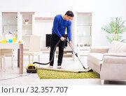 Купить «Young man vacuum cleaning his apartment», фото № 32357707, снято 13 марта 2018 г. (c) Elnur / Фотобанк Лори
