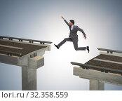 Купить «Young businessman jumping over the bridge», фото № 32358559, снято 28 января 2020 г. (c) Elnur / Фотобанк Лори