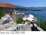 Купить «Budva, Montenegro - June 13.2019. Landscape with a cafe on background of sea in the Old Town», фото № 32359199, снято 13 июня 2019 г. (c) Володина Ольга / Фотобанк Лори