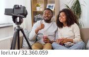 Купить «couple of video bloggers with camera at home», видеоролик № 32360059, снято 17 октября 2019 г. (c) Syda Productions / Фотобанк Лори