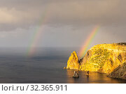 Scenic view from Jasper beach near St. George Monastery to Cape Fiolent in rainy day with rainbow. Rocky coast black sea and cliff, Sevastopol, Crimea, Russia. Landscape Mountains surround the bay. (2019 год). Редакционное фото, фотограф Алексей Ширманов / Фотобанк Лори
