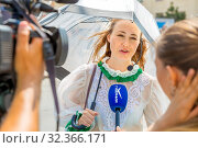 Russia, Samara, July 2019: Gastronomic festival. A girl in a suit gives an interview to the Gubernia TV Channel. Text in Russian: Gubernia. Редакционное фото, фотограф Акиньшин Владимир / Фотобанк Лори