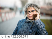 Женщина средних лет на улице разговаривает по телефону. Стоковое фото, фотограф Игорь Низов / Фотобанк Лори