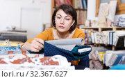 Купить «Brunette choosing fabric in store», фото № 32367627, снято 7 февраля 2019 г. (c) Яков Филимонов / Фотобанк Лори