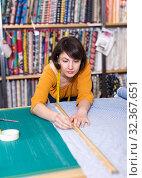 Купить «Saleswoman measuring and cutting off piece of cloth», фото № 32367651, снято 7 февраля 2019 г. (c) Яков Филимонов / Фотобанк Лори