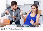 Купить «Upset young man with financial bills having conflict with woman», фото № 32367827, снято 6 июля 2018 г. (c) Яков Филимонов / Фотобанк Лори