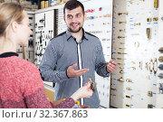 Купить «Young assistant helping female customer», фото № 32367863, снято 5 апреля 2017 г. (c) Яков Филимонов / Фотобанк Лори