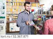 Купить «Smiling male seller assisting woman in choosing floor protectors in shop», фото № 32367871, снято 5 апреля 2017 г. (c) Яков Филимонов / Фотобанк Лори
