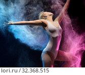 Купить «Woman in color dust cloud streches up gracefully», фото № 32368515, снято 24 декабря 2016 г. (c) Гурьянов Андрей / Фотобанк Лори