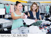 Купить «Smiling female friends choosing trousers in shop», фото № 32368963, снято 19 июня 2017 г. (c) Яков Филимонов / Фотобанк Лори