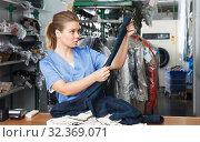 Купить «Worker of laundry checking clothes», фото № 32369071, снято 9 мая 2018 г. (c) Яков Филимонов / Фотобанк Лори