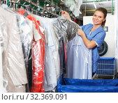 Купить «Worker checking clean clothes in laundry+», фото № 32369091, снято 9 мая 2018 г. (c) Яков Филимонов / Фотобанк Лори