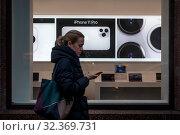Купить «Девушка идет по улице с мобильным телефоном на фоне рекламы телефона Iphone 11 Pro в магазине на Тверской улице города Москвы, Россия», фото № 32369731, снято 4 ноября 2019 г. (c) Николай Винокуров / Фотобанк Лори