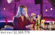 Купить «Bored young blonde woman sitting by the bartender stand and stirs the drink with a straw», видеоролик № 32369779, снято 19 февраля 2020 г. (c) Константин Шишкин / Фотобанк Лори