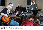 Купить «Young woman guitar player and singer with band», фото № 32383155, снято 26 октября 2018 г. (c) Яков Филимонов / Фотобанк Лори