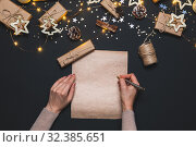 Happy New year 2020. Woman's hands writing Goals on Kraft paper decorated with Christmas Gold and silver decorations on black background. New year concept. Flat lay, top view, copy space. Стоковое фото, фотограф Сергей Тимофеев / Фотобанк Лори