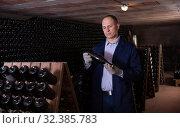 Winemaker checking bottles with wine. Стоковое фото, фотограф Яков Филимонов / Фотобанк Лори