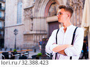 Купить «young European guy in shirt and trousers with suspenders walking around city», фото № 32388423, снято 27 июня 2018 г. (c) Татьяна Яцевич / Фотобанк Лори