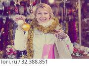 Купить «Positive mature female buying decoration at Christmas Fair», фото № 32388851, снято 21 декабря 2017 г. (c) Яков Филимонов / Фотобанк Лори