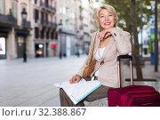 Купить «Adult woman 50-60 years old is sitting with map and suitcase», фото № 32388867, снято 3 сентября 2017 г. (c) Яков Филимонов / Фотобанк Лори