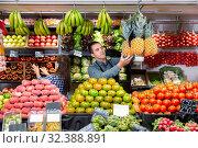 Купить «Friendly man and woman laying out vegetables and fruits in shop», фото № 32388891, снято 6 августа 2020 г. (c) Яков Филимонов / Фотобанк Лори