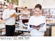 Купить «Portrait of intelligent preteen girl browsing textbooks in public library», фото № 32389191, снято 22 февраля 2018 г. (c) Яков Филимонов / Фотобанк Лори