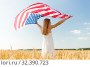 girl with american flag waving over cereal field. Стоковое фото, фотограф Syda Productions / Фотобанк Лори