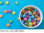 Купить «candy drops in paper cup on blue background», фото № 32390863, снято 11 декабря 2018 г. (c) Syda Productions / Фотобанк Лори