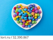 Купить «candies on heart shaped plate over blue background», фото № 32390867, снято 11 декабря 2018 г. (c) Syda Productions / Фотобанк Лори