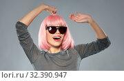 Купить «happy woman in pink wig and sunglasses dancing», фото № 32390947, снято 30 сентября 2019 г. (c) Syda Productions / Фотобанк Лори