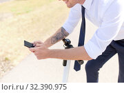 Купить «businessman with smartphone and electric scooter», фото № 32390975, снято 1 августа 2019 г. (c) Syda Productions / Фотобанк Лори